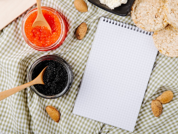 Вид сверху банку красной и черной икры с деревянными ложками миндального творога, хрустящие хрустящие хлебцы и копией пространства на столе