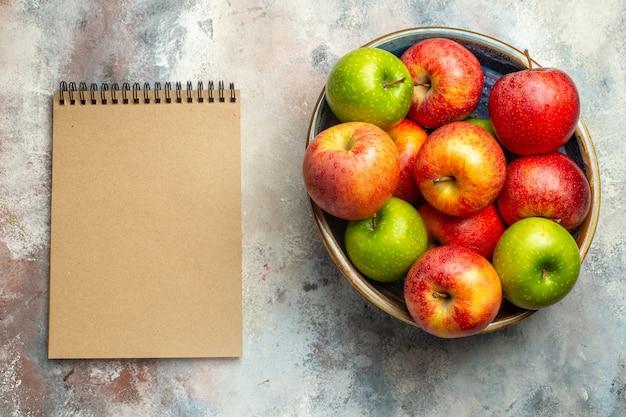Вид сверху красные и зеленые яблоки в миске и блокнот на обнаженной поверхности
