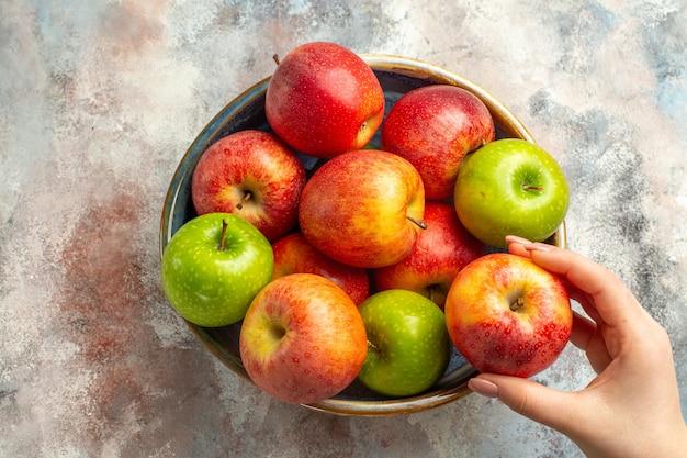 Вид сверху красные и зеленые яблоки в миске, яблоко в женской руке на обнаженной поверхности