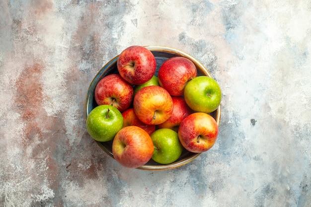 裸の表面のコピー場所のボウルに赤と緑のリンゴの上面図