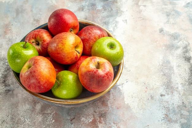 裸の表面のコピースペースのボウルに赤と緑のリンゴの上面図