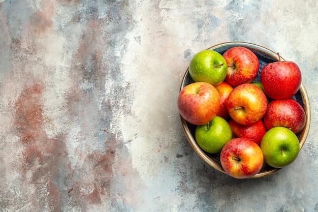 Вид сверху красные и зеленые яблоки в миске на обнаженной поверхности копией пространства