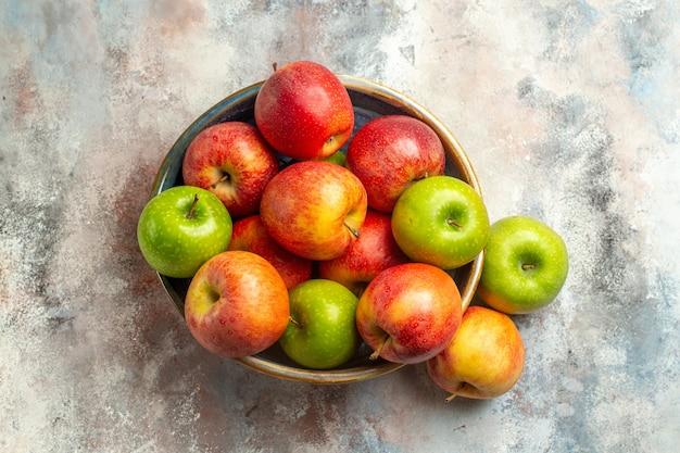 Вид сверху красные и зеленые яблоки в миске на обнаженной поверхности с местом для копирования