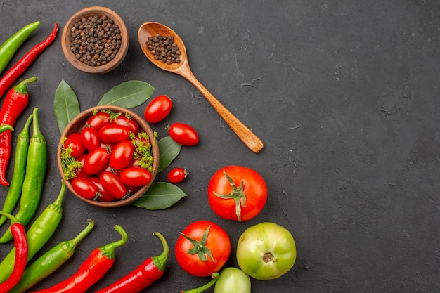Вид сверху красный и зеленый перец и миска помидоров черри, черный перец и красные и зеленые помидоры в левой части черной поверхности