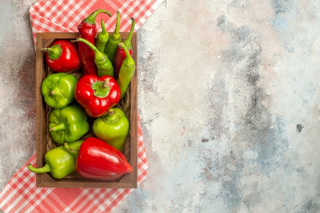 Вид сверху красный и зеленый перец острый перец в деревянной коробке на клетчатой скатерти на обнаженной поверхности свободное место