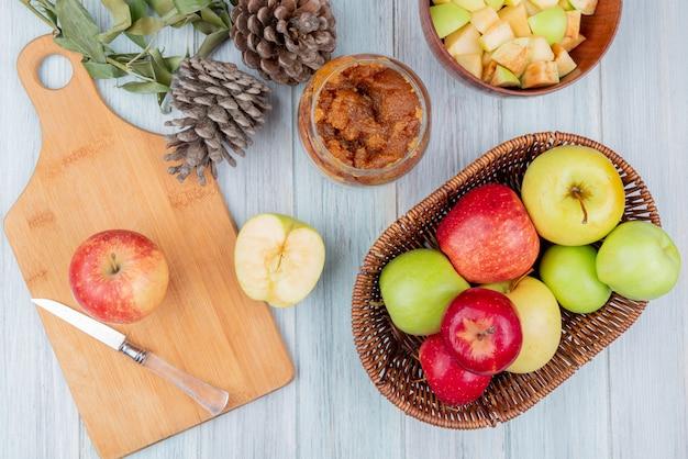 Vista dall'alto di mela rossa e coltello sul tagliere con cesto di mele vasetto di marmellata di mele ciotola di cubetti di mele pigne e foglie su fondo in legno