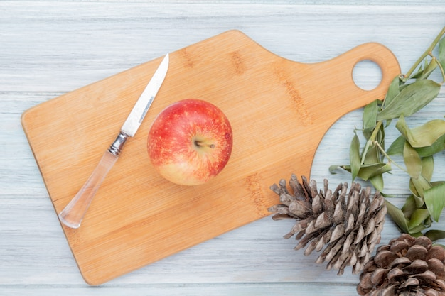 Top view of red apple and knife on cutting board with pinecones and leaves on wooden background