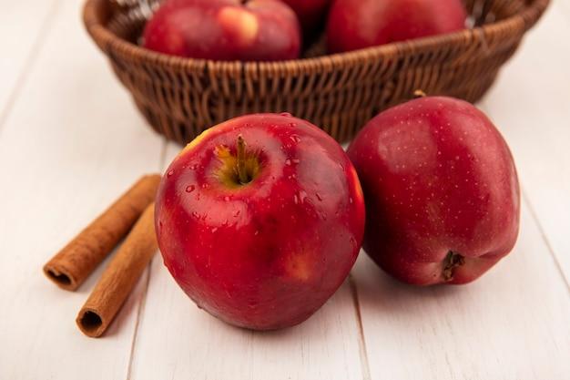 Vista dall'alto di una mela rossa con le mele su un secchio con bastoncini di cannella isolato su una superficie di legno bianca