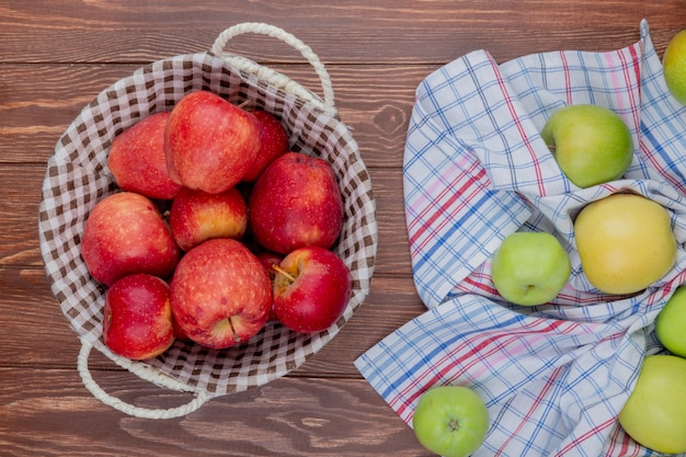 Top view of red apples in basket with green ones on plaid cloth on wooden background
