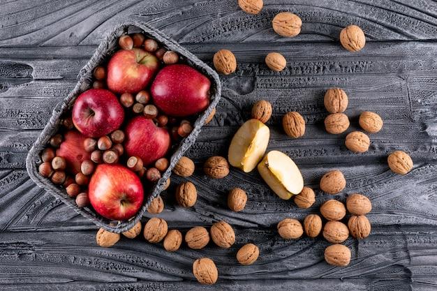 Вид сверху красные яблоки в корзине с орехами и грецкими орехами на серой деревянной горизонтали 1