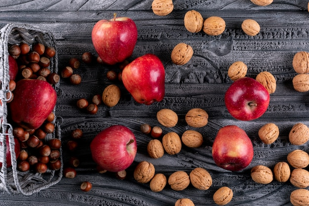 Вид сверху красные яблоки в корзине с орехами и грецкими орехами на серой деревянной горизонтали
