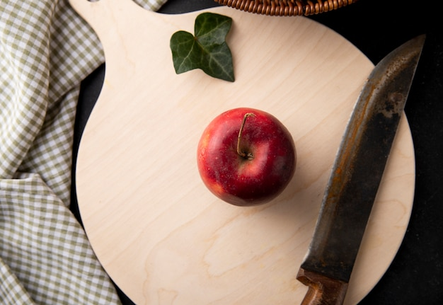 Top view red apples and a knife on the board