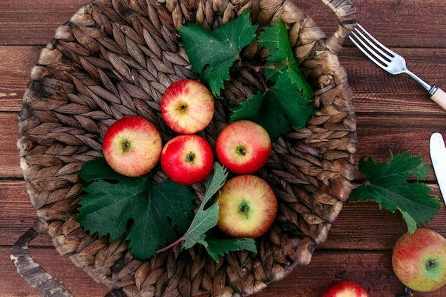 Top view red apples in a wicker basket with leaves