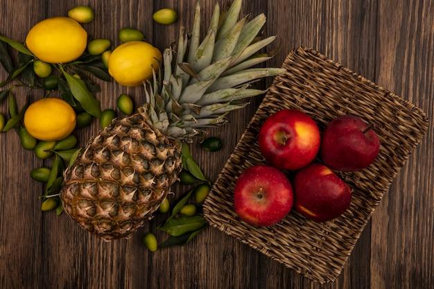 Vista dall'alto di mele rosse su un vassoio di vimini con ananas limoni e kinkan isolati su una superficie di legno