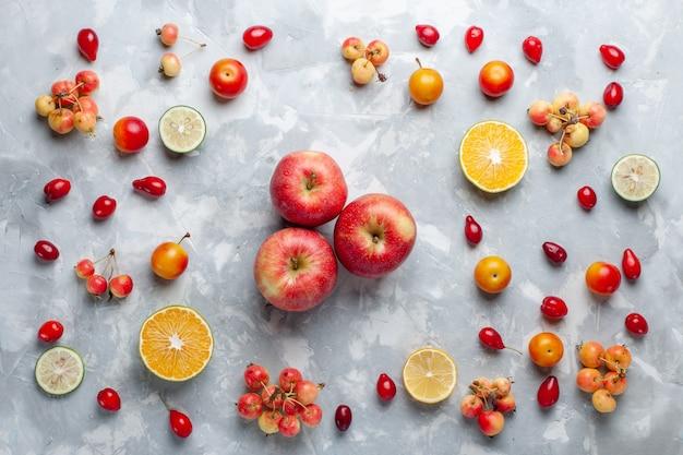 Vista dall'alto mele rosse con limone e ciliegie sulla scrivania bianca
