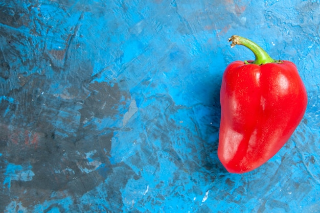 Top view of red bell-pepper on blue surface