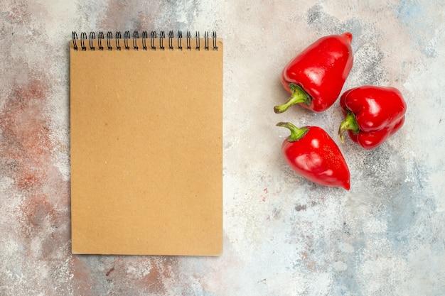 裸の表面の空きスペースに赤ピーマンノートブックの上面図