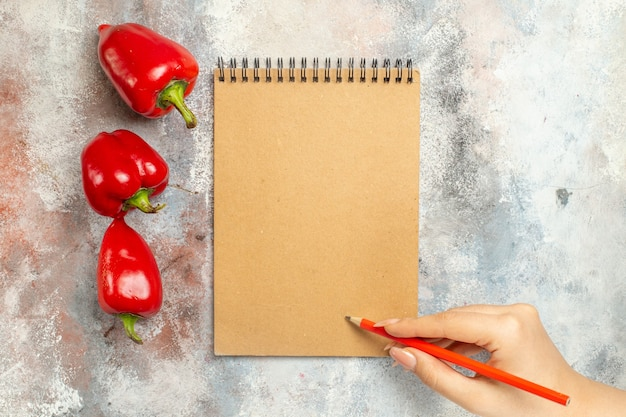 Top view red bell peppers a notebook red pencil in woman hand on nude surface free space