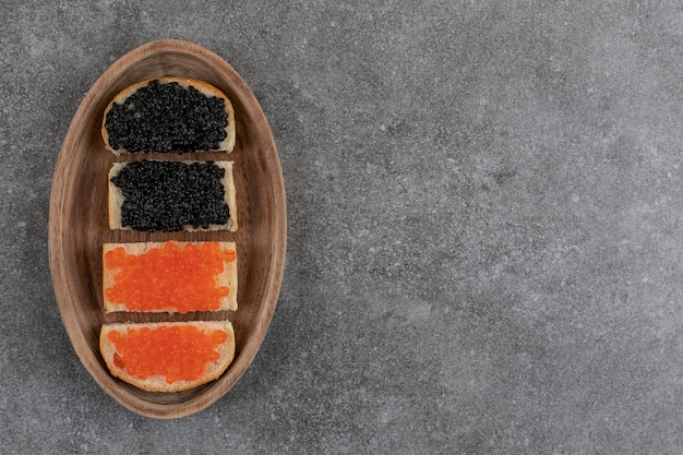 Top view of red and black caviar sandwiches.