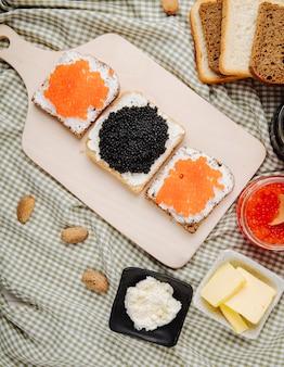 Vista dall'alto caviale rosso e nero toast segale e pane bianco con ricotta caviale rosso caviale nero e mandorla sul tavolo