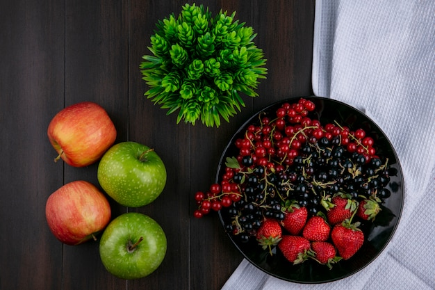 Top view red and black currants with strawberries on a plate with apples on a wooden background