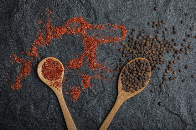 Top view of red and black peppercorns with wooden spoon over black background. close up photo.