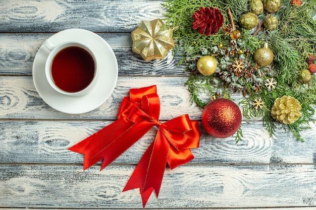 Vista dall'alto fiocco rosso una tazza di tè rami di abete su superficie di legno