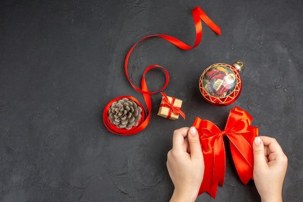 ベージュの表面に赤い弓のクリスマスの装飾品の上面図