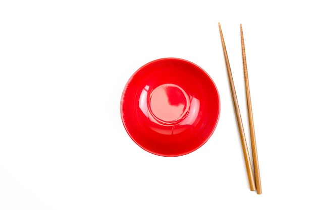 Top view of red bowl with wooden chopsticks isolated