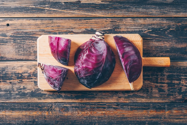 Top view red cabbage in cutting board with sliced cabbage on dark wooden background. horizontal