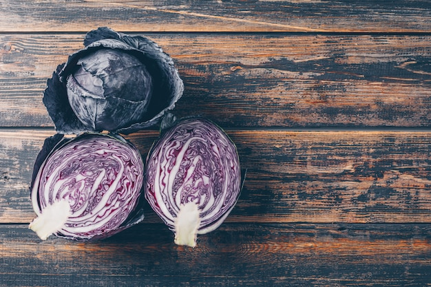 Top view red cabbage with one of them cut in a half on dark wooden background. space for text