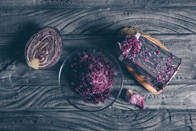 Top view red cabbage with vegetable grater and grated cabbage on dark wooden background. horizontal