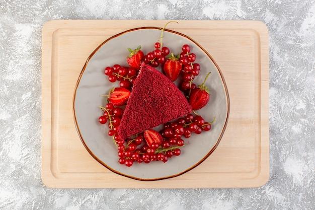 木製のデスクケーキの甘いビスケットに新鮮なクランベリーとイチゴのプレート内の平面図赤いケーキスライスフルーツケーキ作品