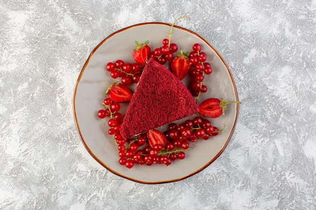 灰色の背景のケーキの甘いビスケットティーに新鮮なクランベリーとプレート内の平面図赤いケーキスライスフルーツケーキピース
