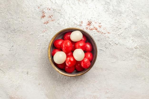 Вид сверху красные конфеты внутри тарелки на белом фоне конфеты сахарная конфета вкусное сладкое