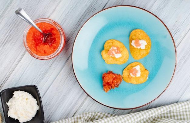 Вид сверху закуска из красной икры, картофельные чипсы, сыр творог и красная икра на вершине
