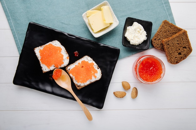 Top view red caviar toast rye bread with cottage cheese butter wooden spoon and almond