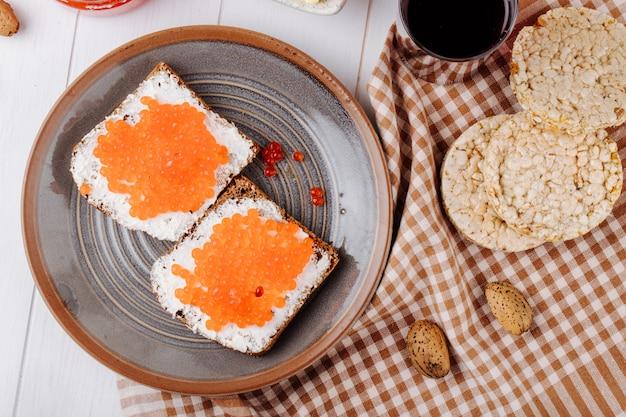Вид сверху красная икра тост ржаной хлеб с творогом красная икра стакан вишневого сока хрустящие хлебцы и миндаль на столе