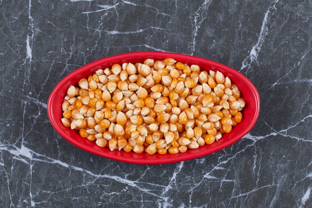 Top view of red ceramic bowl full with corn seeds.