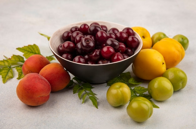 Top view of red cherries on a black bowl with fresh and juicy peaches with green cherry plums isolated on a white background