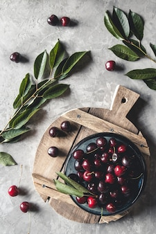 Top view of red cherries on a bowl with slices of peaches on a wooden kitchen board with knife on a concrete background