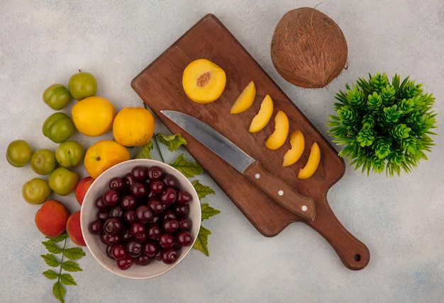 Top view of red cherries on a bowl with slices of peaches on a wooden kitchen board with knife on a white background