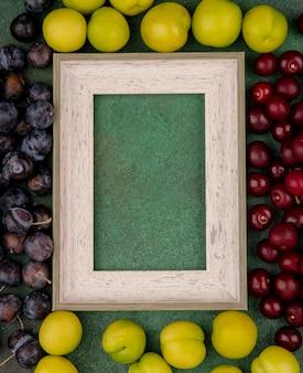 Vista dall'alto di ciliegie rosse con prugnole viola scuro con prugne ciliegia verdi su sfondo verde con spazio di copia