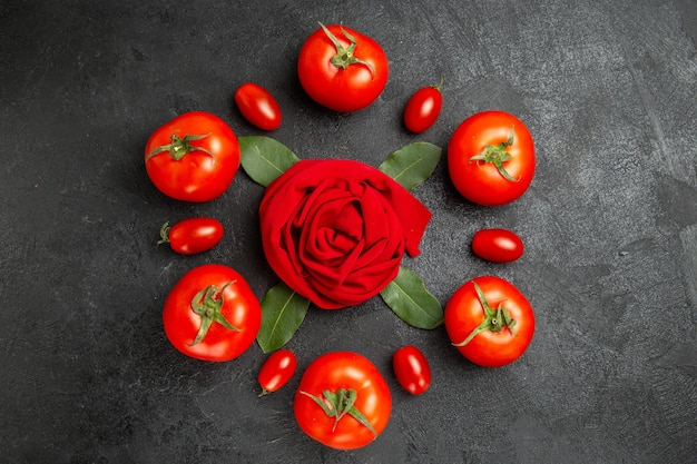 Top view red and cherry tomatoes around a towel in rose shape and bay leaves on dark ground with copy space