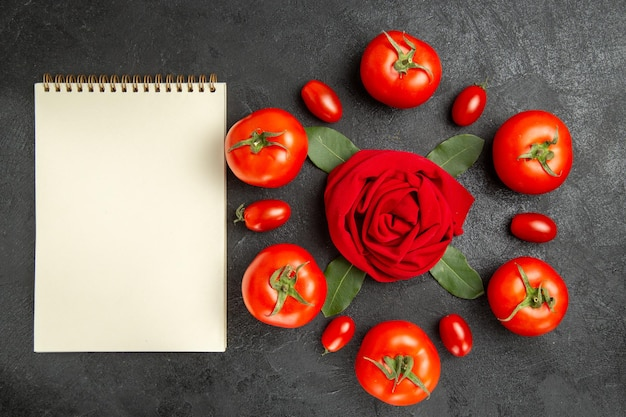 Top view red and cherry tomatoes around a towel in rose shape and bay leaves and a notebook on dark ground