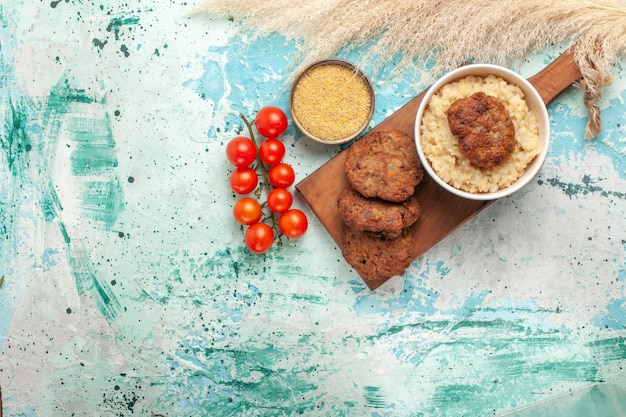 上面図青い表面に肉カツレツと赤いチェリートマト