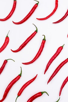 Top view red chili pepper pattern on white  vertical