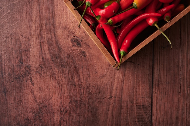 Top view of red chili peppers in a box on wooden surface with space for text