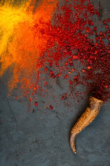 Top view of red chilli and sumac powder spices with curry on black