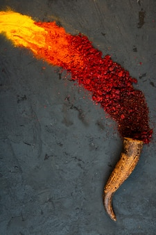 Top view of red chilli and sumac powder spices with curry scattered from a horn on black